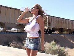 Kelly pours water on her white tank to cool down in the desert then gets fucked while pressed up against a train.