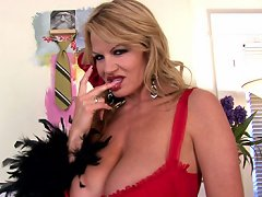 Kelly Madison shakes her big tits in red bra and garter belt then bangs her cunt with a red dildo.